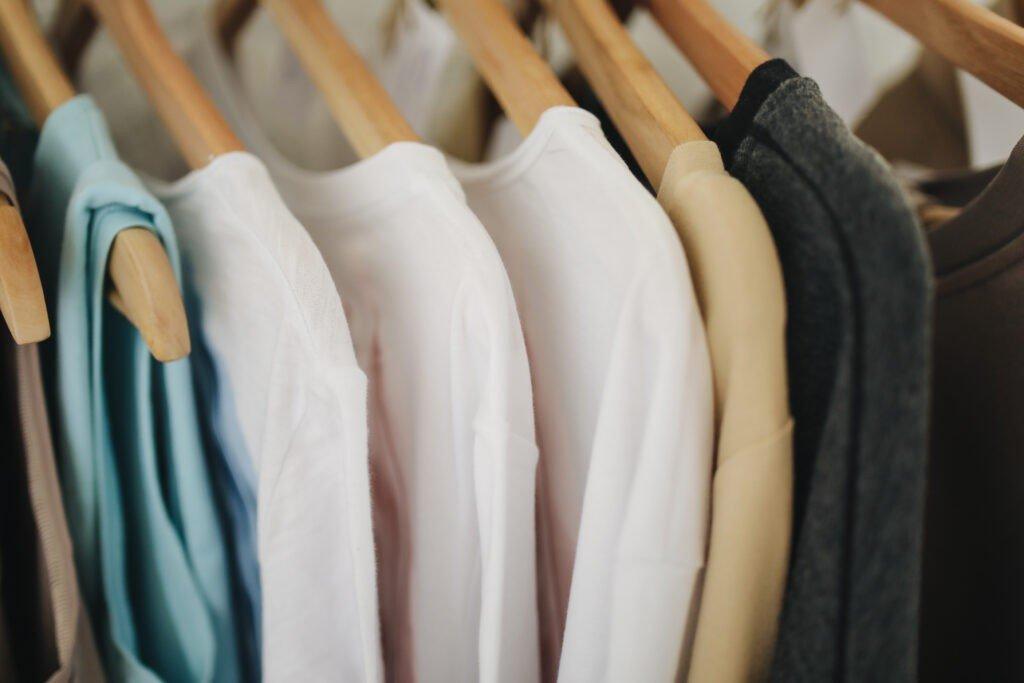 Ubrania porozwieszane w równych odstępach na wieszakach, sugerują dobry nawyk porządku