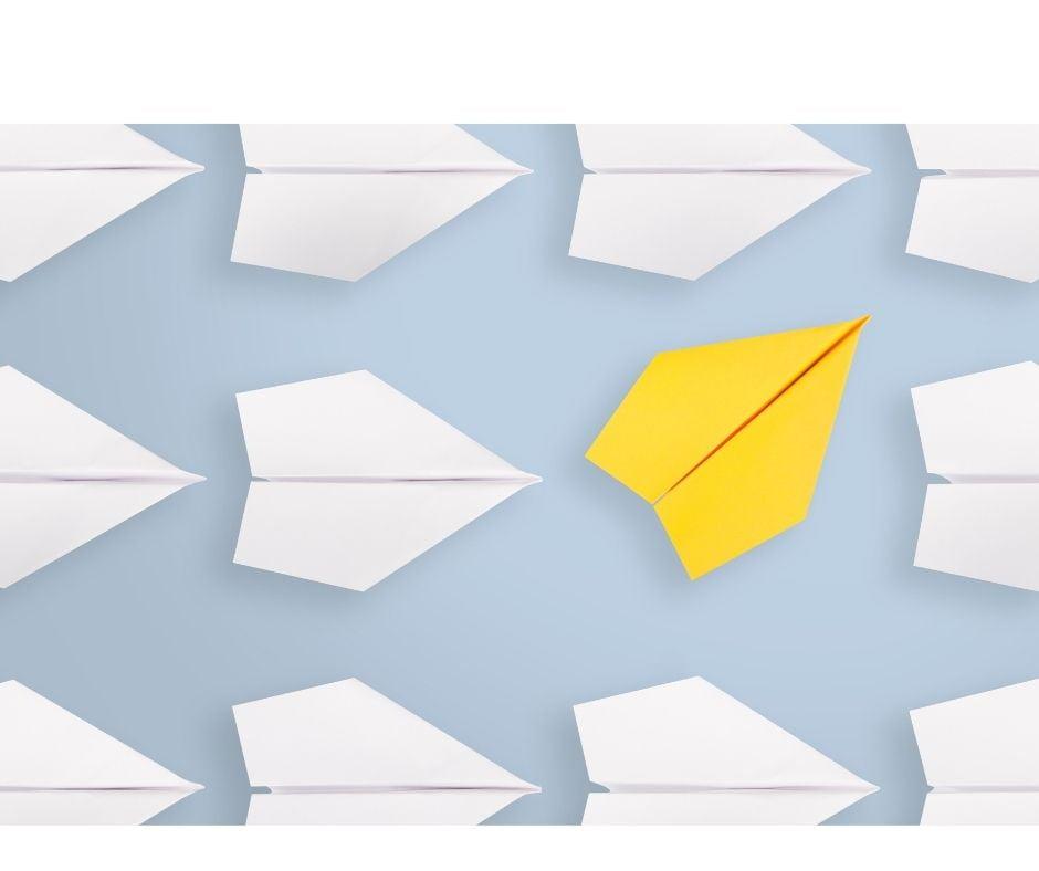 Białe samoloty zrobione z kartek papieru, a pośród nich inny, obrazujący zmianę