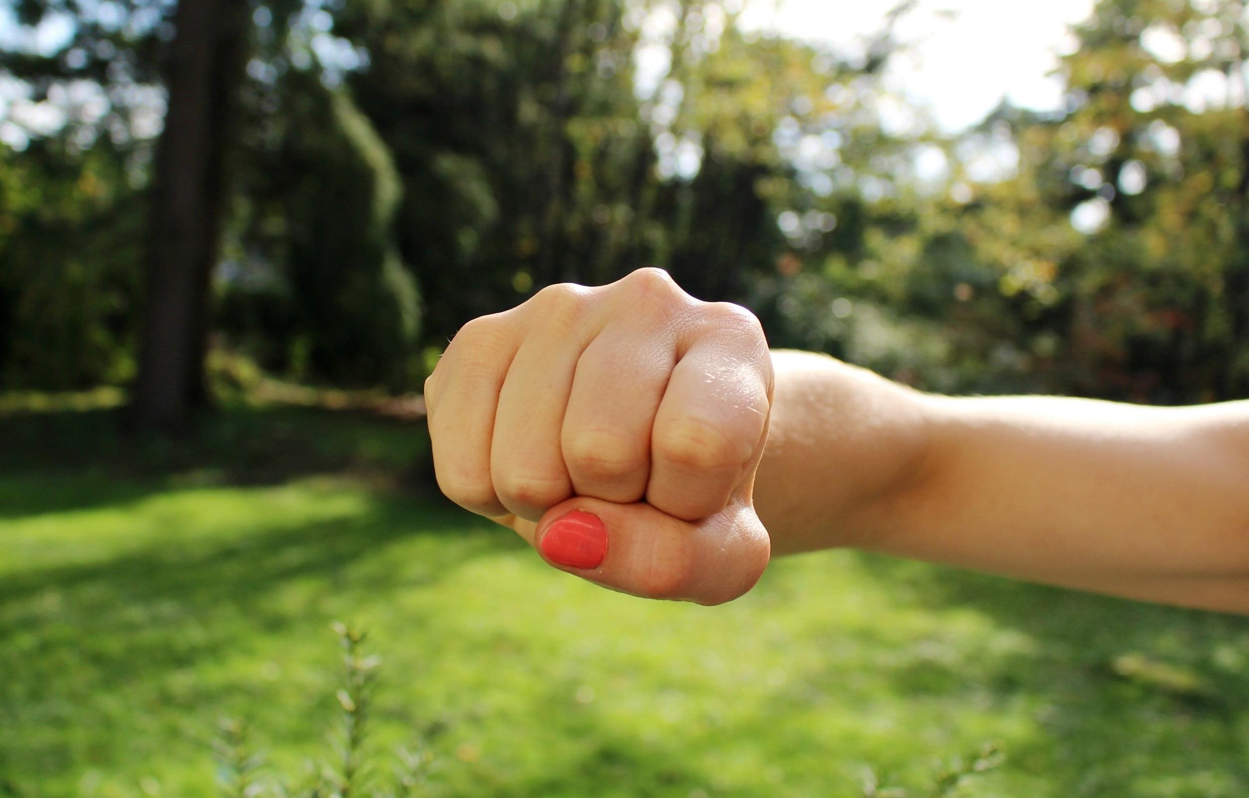 Kobiece ręka ułożona do uderzenia. Dłoń zaciśnięta w pięść, wskazuje na złość i frustrację