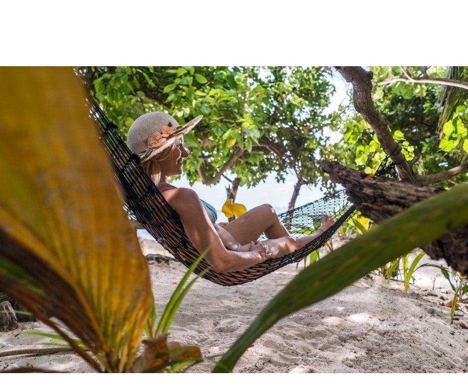 Młoda dziewczyna leży na hamaku rozwieszonym między drzewami. Jest radosna i zrelaksowana