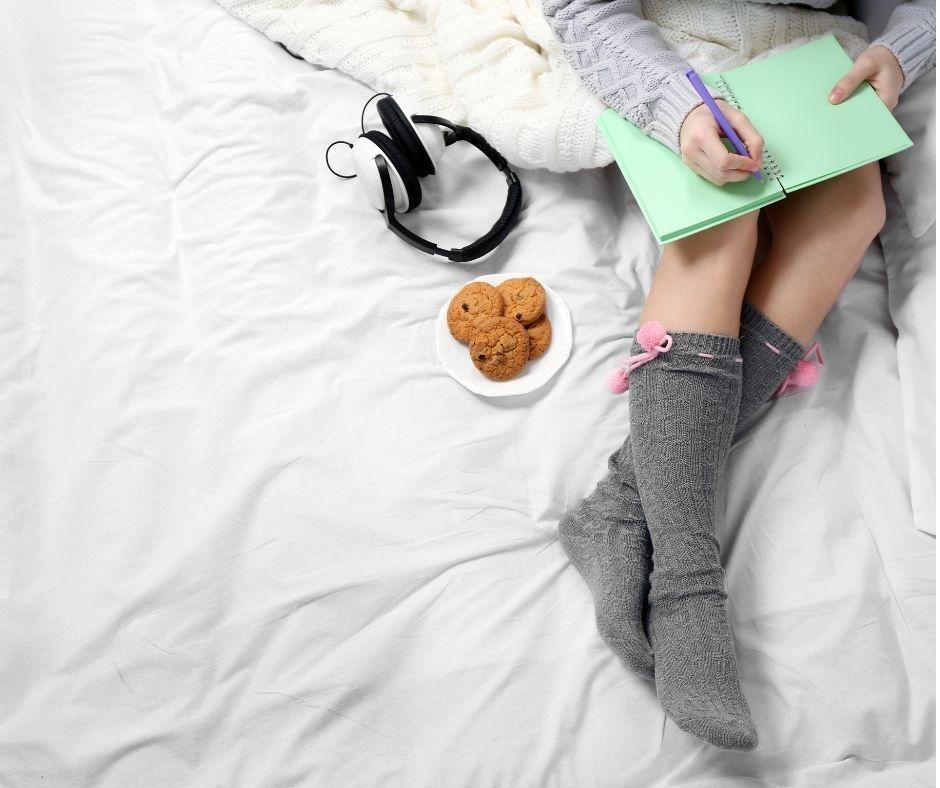 Młoda dziewczyna siedzi na białej pościeli i pisze pamiętnik, zapisuje swoje myśli. Obok niej leżą słuchawki i ciasteczka