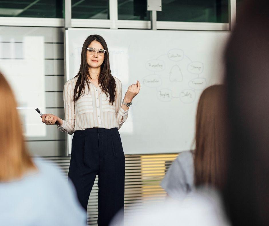 Kobieta robi prezentację, za nią dwie białe tablice w wykresami