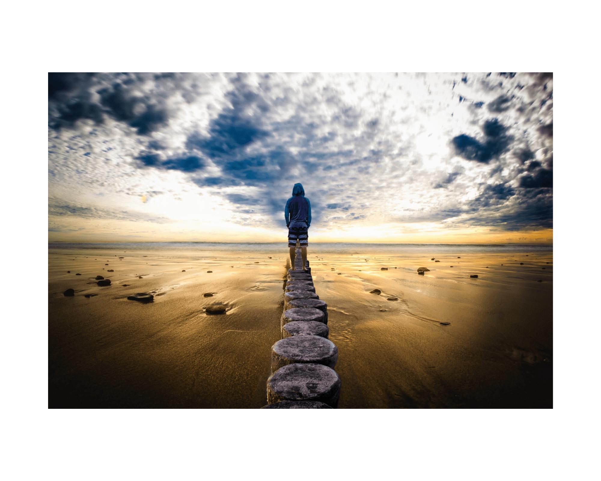 Mężczyzna stoi tyłem, w oddali, zatopiony w swoich myślach, patrzy się w lekko zachmurzone niebo. Wyczuwa się atmosferę wewnętrznego spokoju. Paliki na żółtym piasku, cisza.