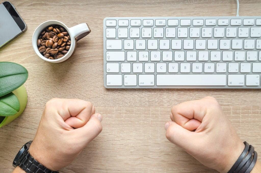 Mężczyzna w pracy przy biurku, zaciśnięte pięści ze złości, nadmiar pracy i obowiązków. Obok stoi filiżanka z ziarnami kawy i klawiatura