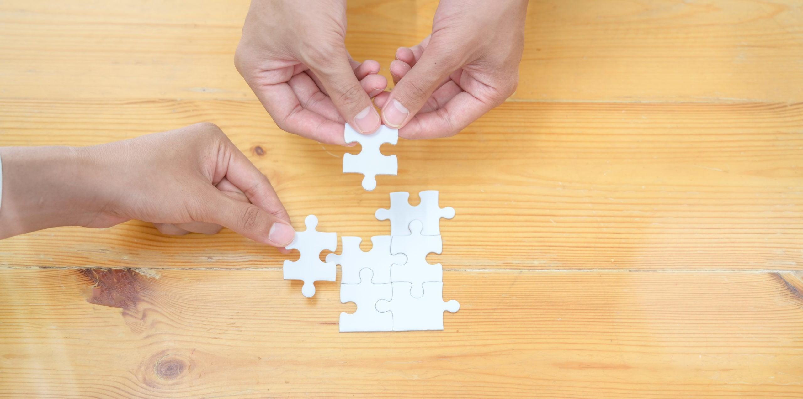 Dwie pary rąk układają puzzle ułożone na drewnianym stole. Jedna osoba ma pulza, który pasuje do dalszej układanki, zna część rozwiązania. dalszy krok