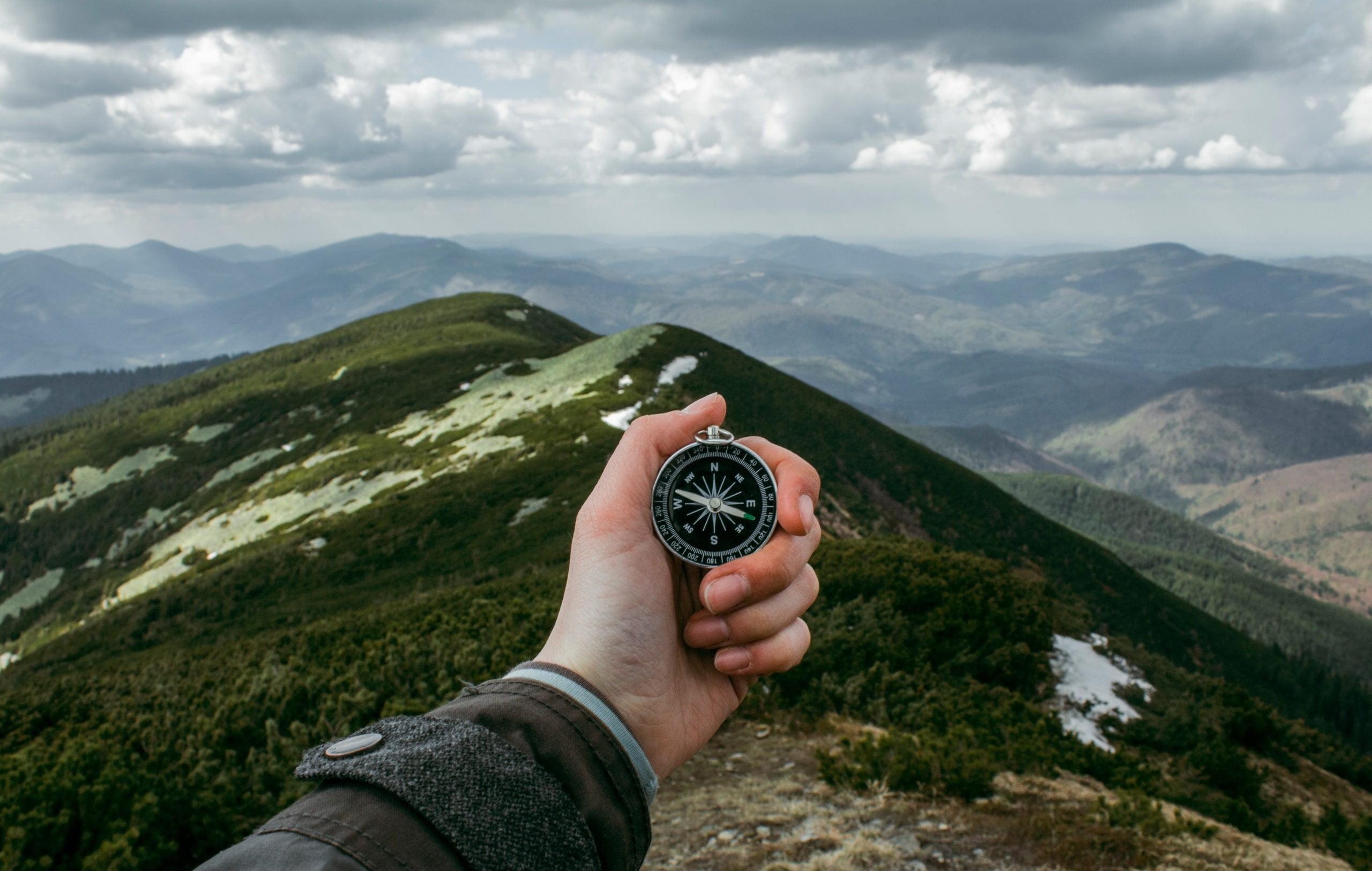 Ręka trzymająca kompas, mężczyzna w drodze na szczyt, szuka właściwego kierunku, właściwej drogi. swojej życiowej misji