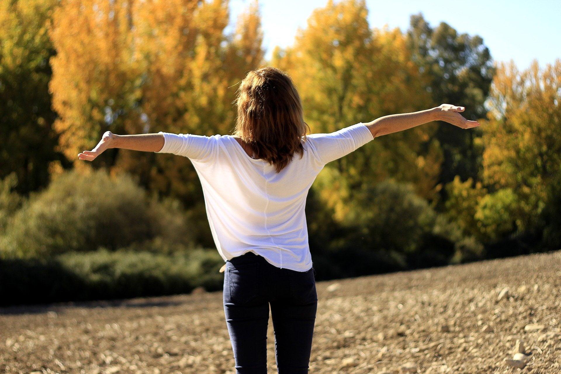 Kobieta w białej bluzce i jeansach stoi tyłem, ma otwarte ramiona, wyraża tym radość i wdzięczność za to co posiada. Jej wzrok skierowany jest na drzewa, symbolizując pełnie życia