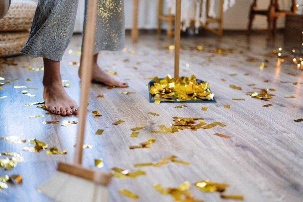 Kobieta,, widać jej tylko nogi trzyma szczotkę i sprząta podłogi, chce żeby było czysto, perfekcyjnie, ale rozsypały się błyszczące papiery i znowu nie jest idealnie