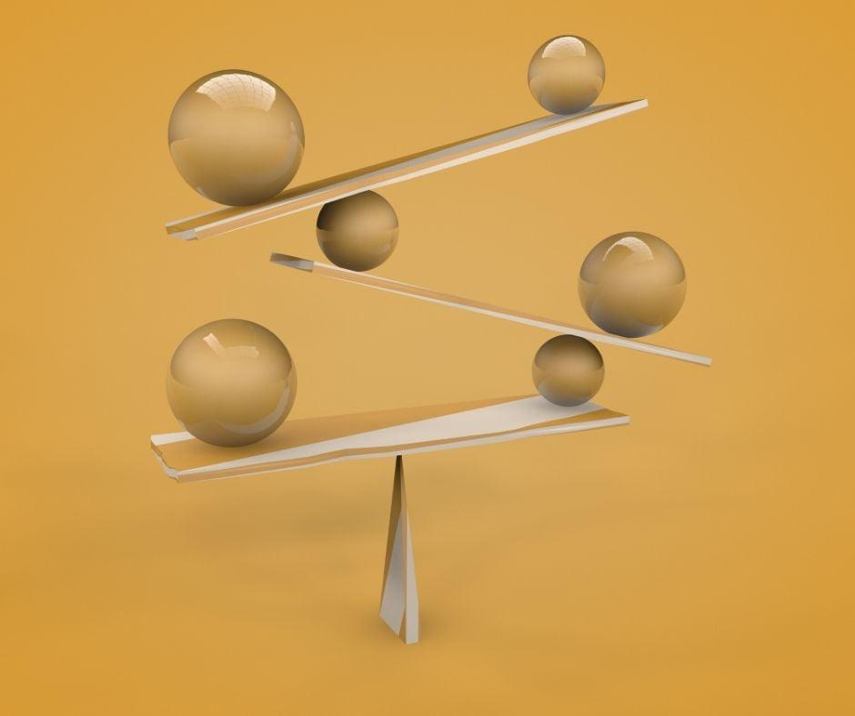 Kule ułożone na trzech poziomach. Leżą na deskach, kule są różnej wielkości i balansują tworząc równoważny układ.