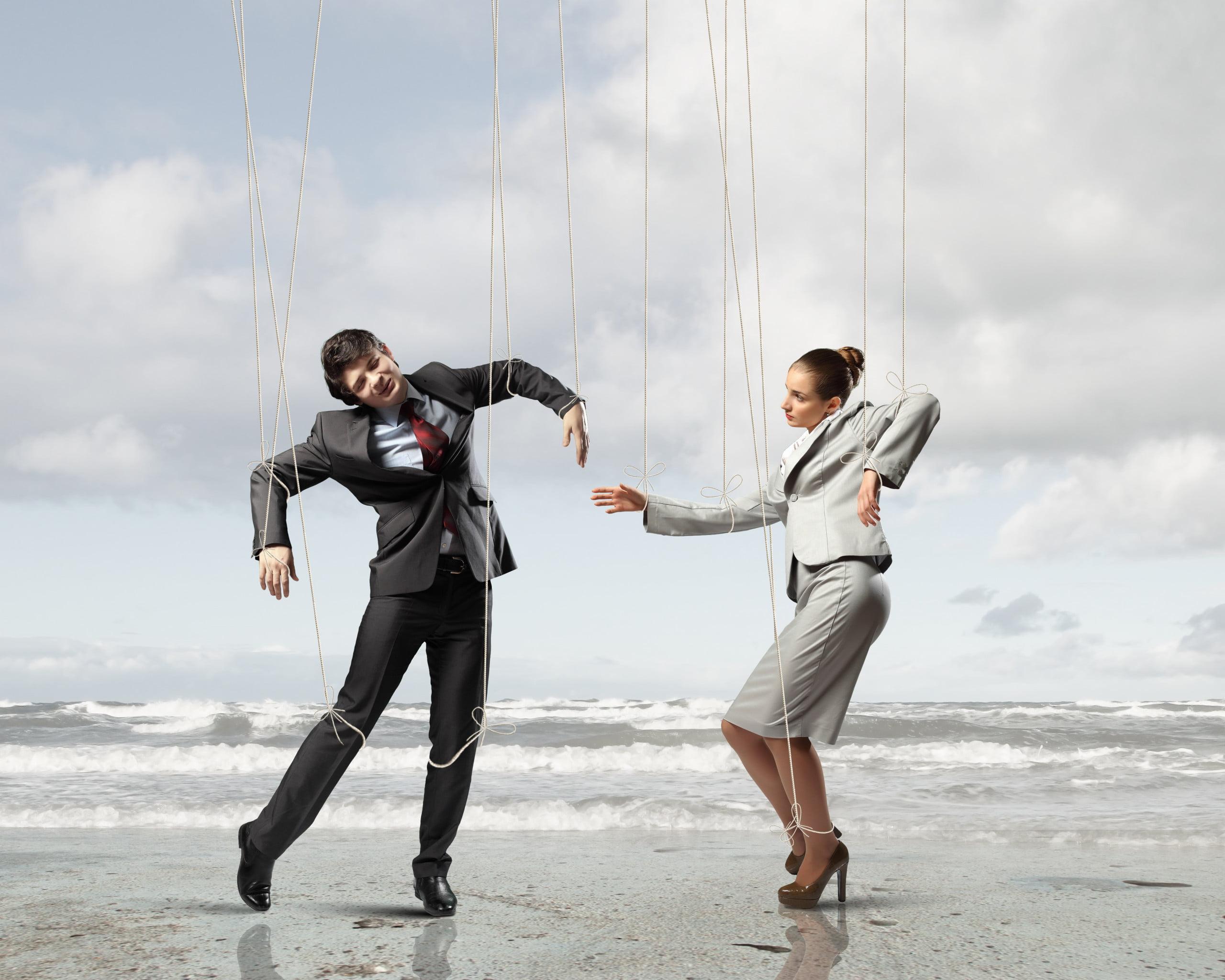 Kobieta i mężczyzna na sznurkach jak kukiełki, wykonuje ruchy które nie są sterowane nie przez nich