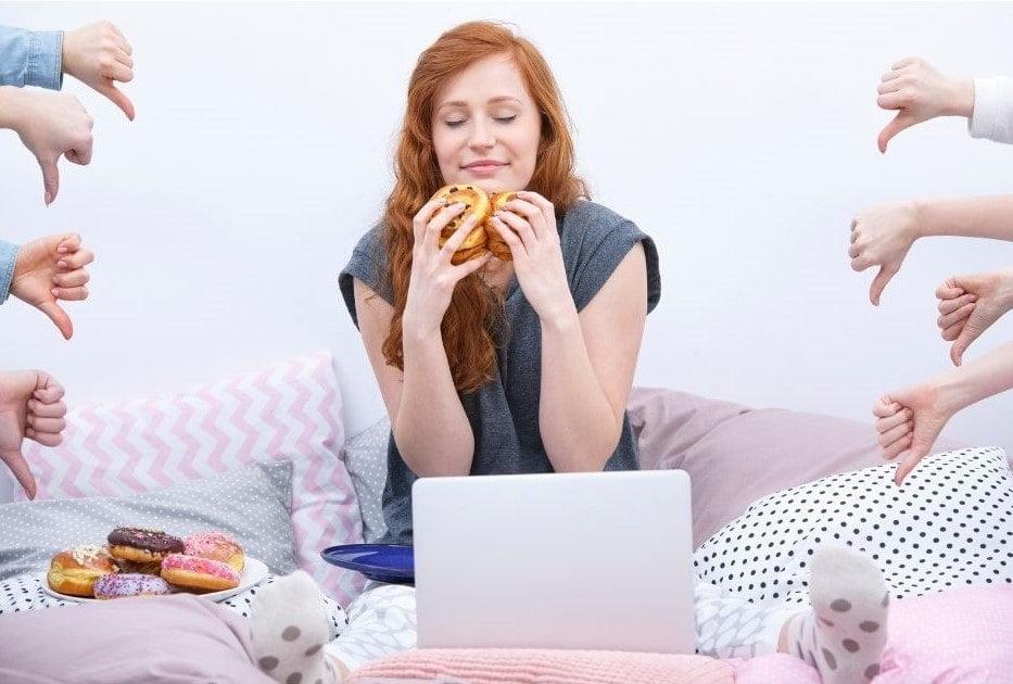 Kobieta siedzi na łóżku przed je hamburgera, chociaż ma noworoczne postanowienie, że nie będzie tego robić. Wokół niej kciuki skierowane do dołu, pokazujące że to zły nawyk